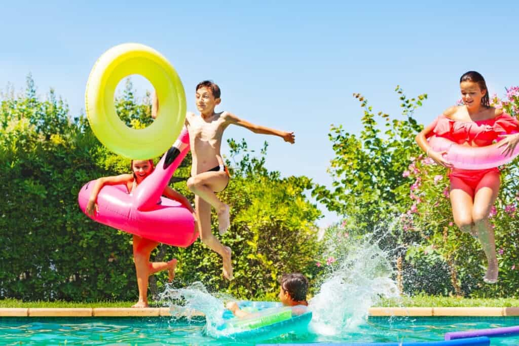 Kid jumping in pool with pool toys
